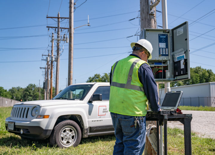 AEP Ohio crew member standing outside, installing smart technology on equipment.